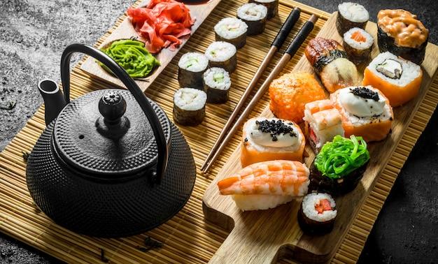 Conjunto de rolos de sushi em um guardanapo com chá verde. na mesa rústica preta