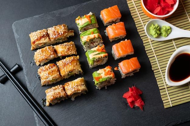 Conjunto de rolos de sushi fresco com enguia, abacate e salmão na placa de ardósia preta.