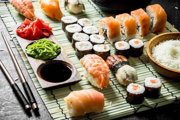 Conjunto de rolos de sushi japonês com molho e pauzinhos. na mesa rústica escura