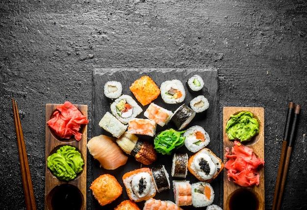 Conjunto de rolos de sushi japonês para dois com molhos e pauzinhos. na mesa rústica preta