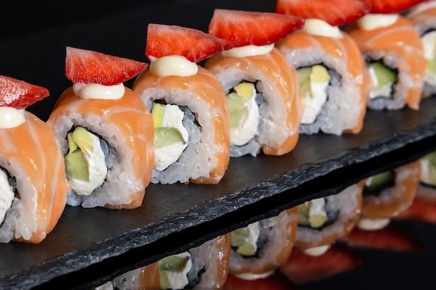 Conjunto de rolos de sushi no fundo da mesa preto