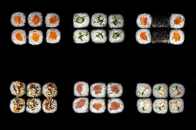 Conjunto de rolos japoneses. um conjunto de pãezinhos e sushi em um fundo preto