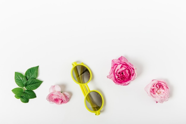 Conjunto de rosas selvagens, folhas e óculos de sol amarelos da moda na vista superior. copie o espaço