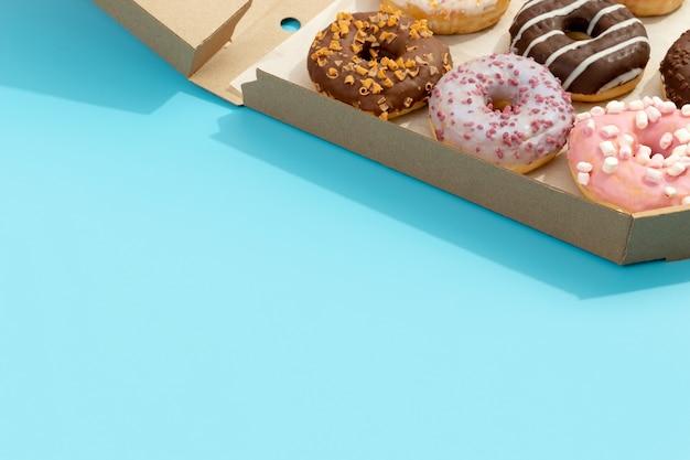 Conjunto de rosquinhas coloridas deliciosas em caixa de papel na entrega online de comida para viagem azul