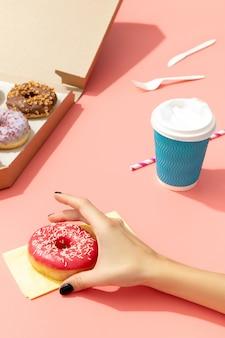 Conjunto de rosquinhas coloridas deliciosas em caixa de papel na superfície rosa