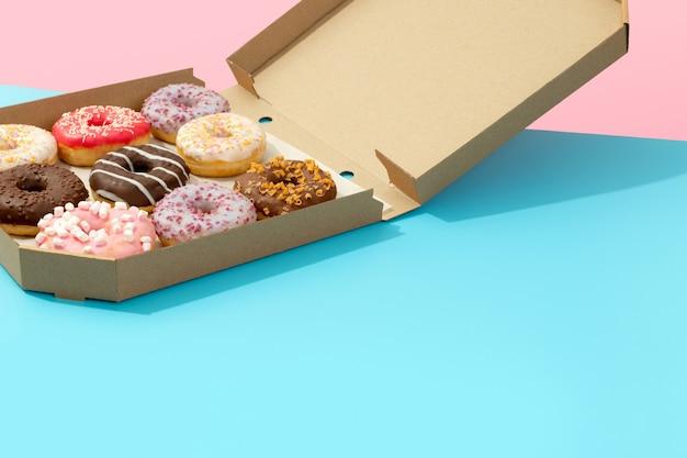 Conjunto de rosquinhas coloridas saborosas em caixa de papel na superfície azul