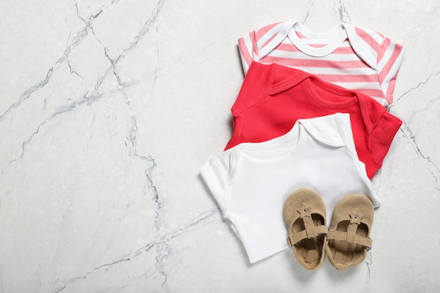 Conjunto de roupa de bebê e sapatos. lugar para texto