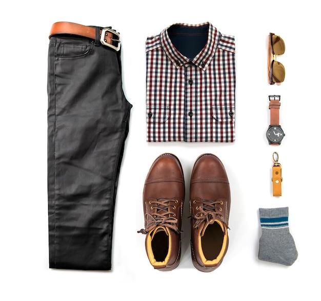 Conjunto de roupa masculina com botas marrons, relógio, jeans azul, cinto, carteira, óculos de sol, camisa preta e pulseira isolado no fundo branco, vista superior