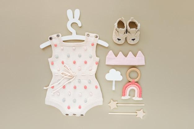 Conjunto de roupas de bebê e acessórios em fundo bege. macacão de malha com pontos no cabide bonito com orelhas de coelho e sapatos, coroa de algodão e brinquedos. recém-nascido da moda. camada plana, vista superior