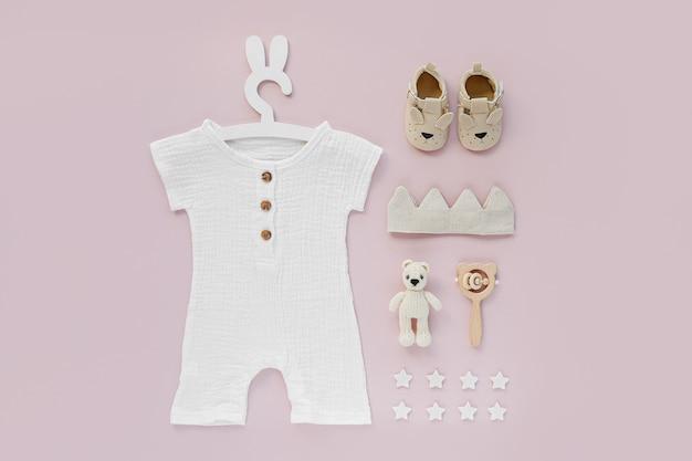 Conjunto de roupas de bebê e acessórios em fundo rosa. body branco no cabide bonito com orelhas de coelho e sapatos, coroa de algodão e brinquedos. recém-nascido da moda. camada plana, vista superior
