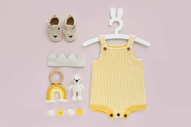 Conjunto de roupas de bebê e acessórios em fundo rosa. macacão de malha amarelo em cabide bonito com orelhas de coelho e sapatos, coroa de algodão e brinquedos. recém-nascido da moda. camada plana, vista superior
