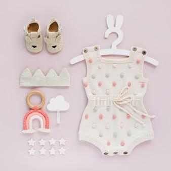 Conjunto de roupas de bebê e acessórios em fundo rosa. macacão de malha com pontos no cabide bonito com orelhas de coelho e sapatos, coroa de algodão e brinquedos. recém-nascido da moda. camada plana, vista superior
