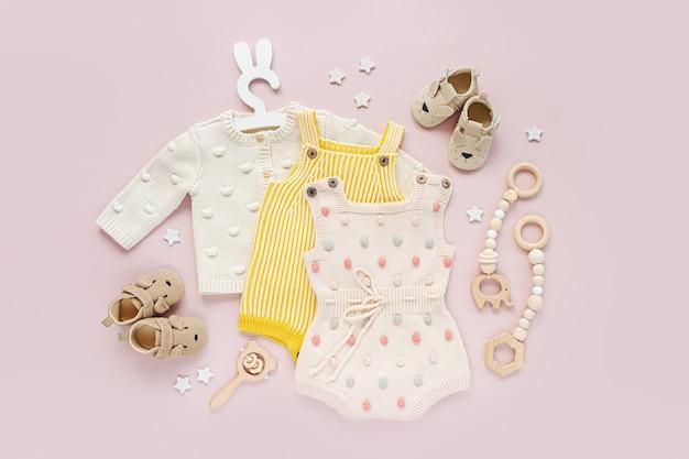 Conjunto de roupas de bebê e acessórios em fundo rosa. vários macacões, sapatos de bebê de macacão e brinquedos. recém-nascido da moda. camada plana, vista superior