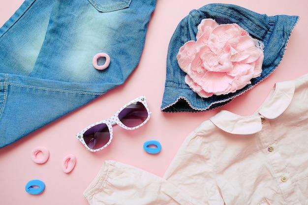 Conjunto de roupas de verão para crianças em fundo rosa. olhar de moda bebê menina