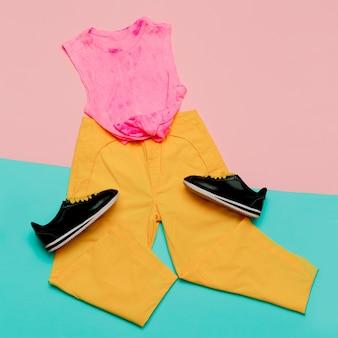 Conjunto de roupas esportivas de moda plana: sapatos, tênis, calças e fundo brilhante superior. estilo urbano. vista do topo.