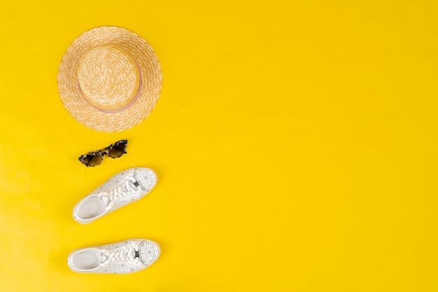 Conjunto de roupas femininas e acessórios em fundo amarelo brilhante
