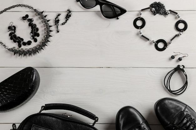 Conjunto de roupas femininas elegantes negras sobre fundo branco de madeira.