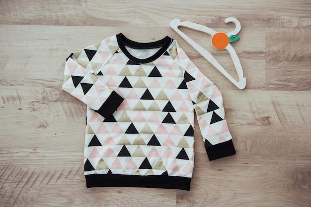 Conjunto de roupas infantis, isolado no fundo de madeira