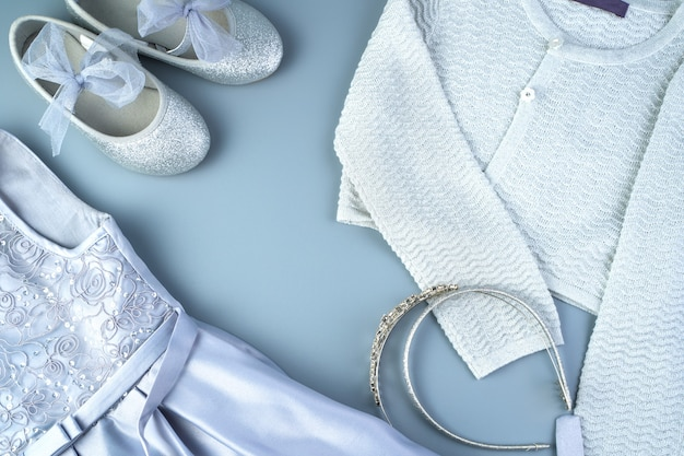 Conjunto de roupas infantis para o feriado em um fundo cinza-azulado.