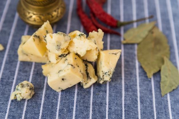 Conjunto de saboroso queijo azul perto de pimenta seca e folhas