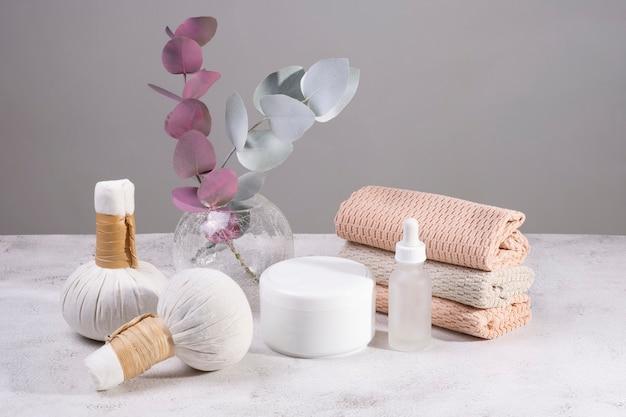 Conjunto de sacos de massagem com ervas, cremes e toalhas em cores claras.