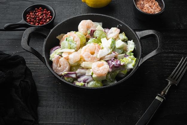 Conjunto de salada com camarão, abacate, tomate e maionese no conjunto de alface, com molho de maçã e uva, na mesa de madeira preta