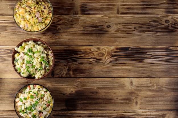Conjunto de saladas de maionese festivas na mesa de madeira. vista do topo