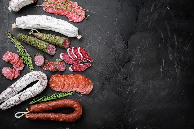 Conjunto de salame curado seco, salsichas espanholas, fatias e cortes na superfície texturizada preta, vista superior com espaço para texto.
