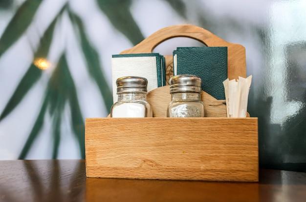 Conjunto de saleiro e pimenteiro de vidro, palitos e guardanapos de papel verde escuro no organizador de madeira na mesa de café.