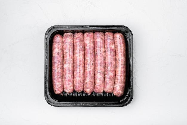 Conjunto de salsichas de carne crua em caixa de embalagem, no fundo da mesa de pedra branca, vista de cima plana lay
