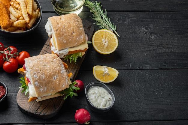 Conjunto de sanduíche de dedos de peixe, em uma tábua de madeira, na mesa de madeira preta