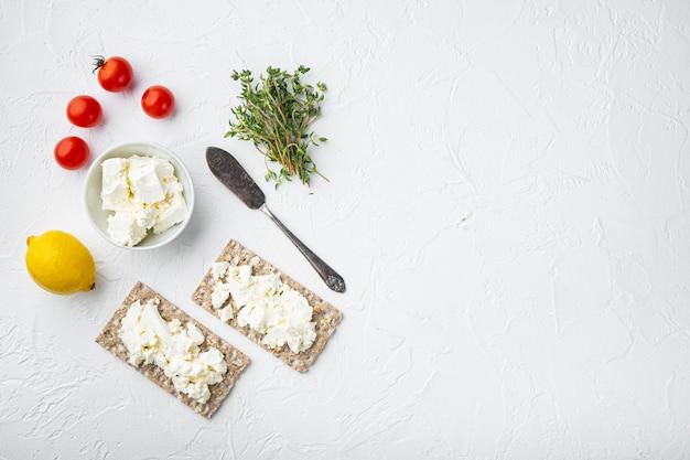 Conjunto de sanduíches de pão torrado, formato quadrado, sobre mesa de pedra branca, vista de cima plano plano