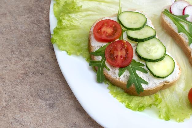 Conjunto de sanduíches vegetarianos com legumes em um prato. sanduíche com queijo cottage, pepino e tomate cereja e rabanete em um prato branco sobre a mesa.