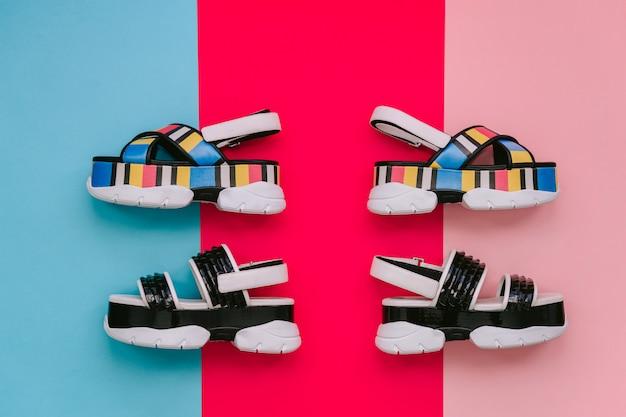 Conjunto de sapatos femininos na moda. sandálias das mulheres multicoloridas na moda de verão na cunha alta na parede azul e rosa. calçado vogu e elegante para meninas modernas.