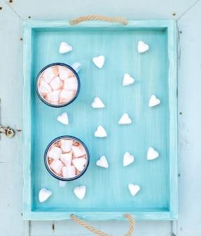 Conjunto de saudação de feriado de são valentim. chocolate quente e marshmallows em forma de coração em canecas de esmalte velhas na bandeja de servir turquesa sobre madeira azul