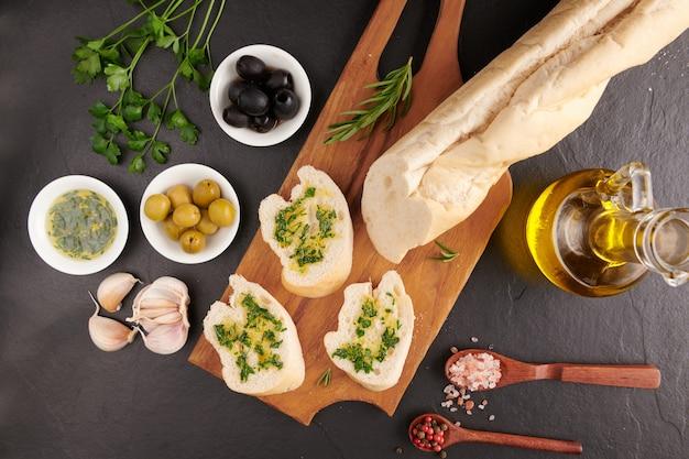 Conjunto de snacks mediterrânicos. azeitonas, azeite, ervas e ciabatta fatiado em uma placa de madeira em uma placa de pedra ardósia preta sobre a superfície escura, vista superior. postura plana.