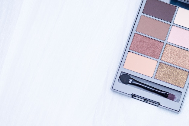 Conjunto de sombras de cosméticos para maquiagem. compõem os fundamentos nus, sobre fundo branco de madeira. postura plana, cópia espaço, conceito de blog.