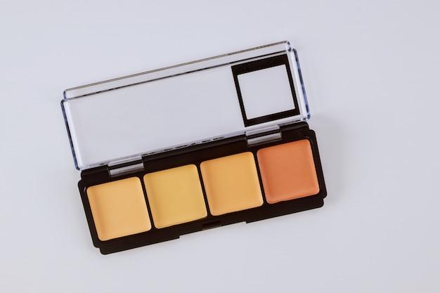 Conjunto de sombras em tons bege pastel paleta marrom sombras foscas, close-up do produto de maquiagem em uma mesa branca isolada
