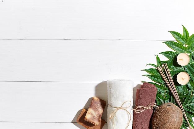 Conjunto de spa com toalha e sabonete em fundo branco de madeira com folhas verdes