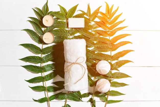 Conjunto de spa com toalha e sabonete em fundo branco de madeira com reflexo solar de folhas verdes