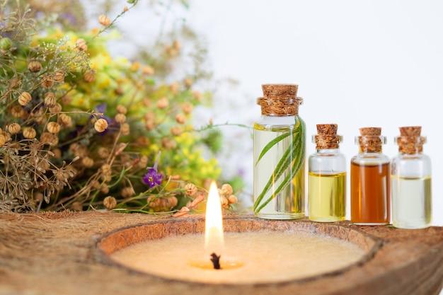 Conjunto de spa com vela acesa, óleos essenciais em garrafas, ervas e flores