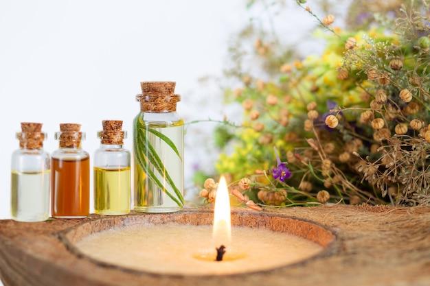 Conjunto de spa de óleos essenciais com vela acesa, ervas saudáveis e flores