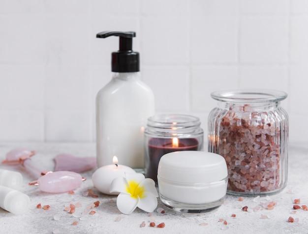 Conjunto de spa, óleo essencial, sal de massagem, velas e flores de frangipani em fundo cinza de concreto