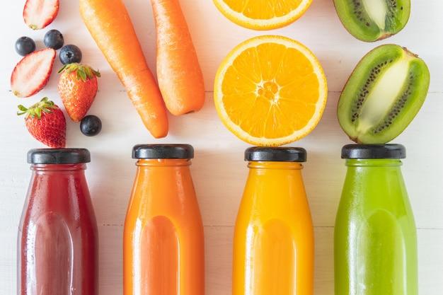 Conjunto de suco de frutas frescas caseiras, fonte natural de vitamina c e suplemento, bebidas saudáveis em garrafa de vidro faly leigos na madeira branca