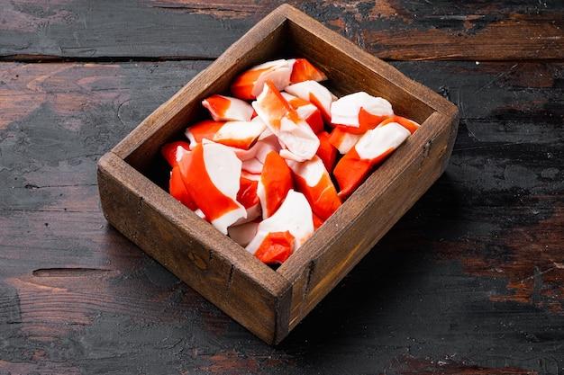 Conjunto de surimi de carne de caranguejo fresco com siri azul, em caixa de madeira, sobre mesa de madeira escura