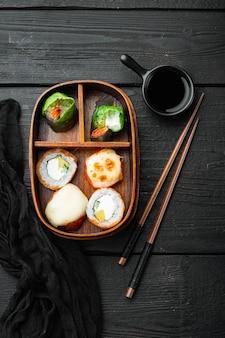 Conjunto de sushi bento box caseiro com sushi rolls, na mesa de madeira preta