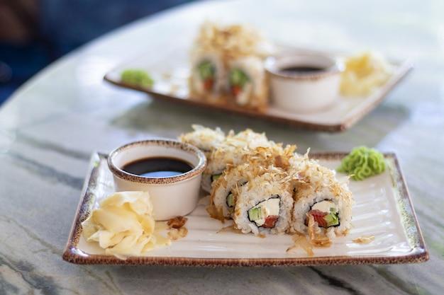 Conjunto de sushi bonito rola com salmão, queijo e atum defumado em flocos. comida tradicional japonesa