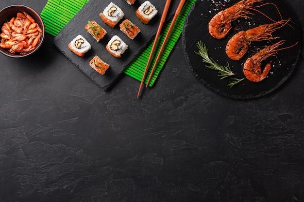 Conjunto de sushi, camarão e maki com uma garrafa de vinho na mesa de pedra. vista superior com espaço para texto