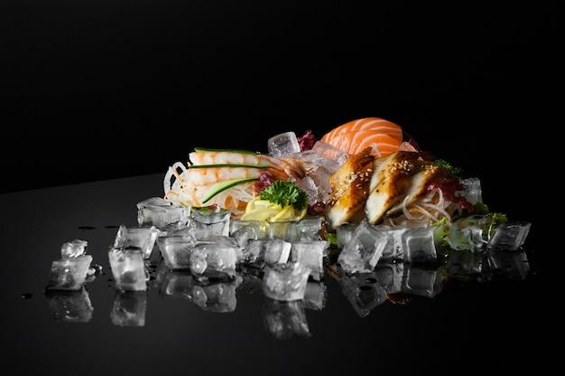 Conjunto de sushi com pedaços de gelo derretido em um fundo preto com reflexo