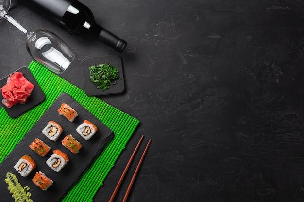 Conjunto de sushi e maki com uma garrafa de vinho na mesa de pedra. vista superior com espaço para texto
